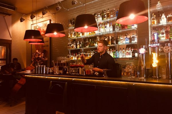 Bartender preparing coctails at bar in Brasserie 66