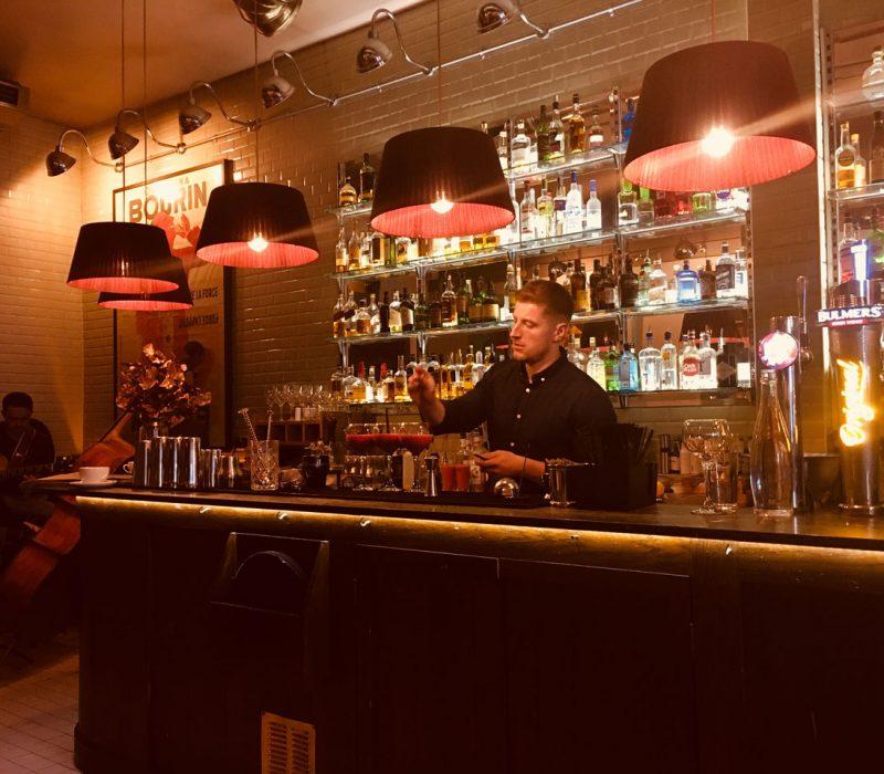 Bartender preparing coctails at bar in Brasserie 66